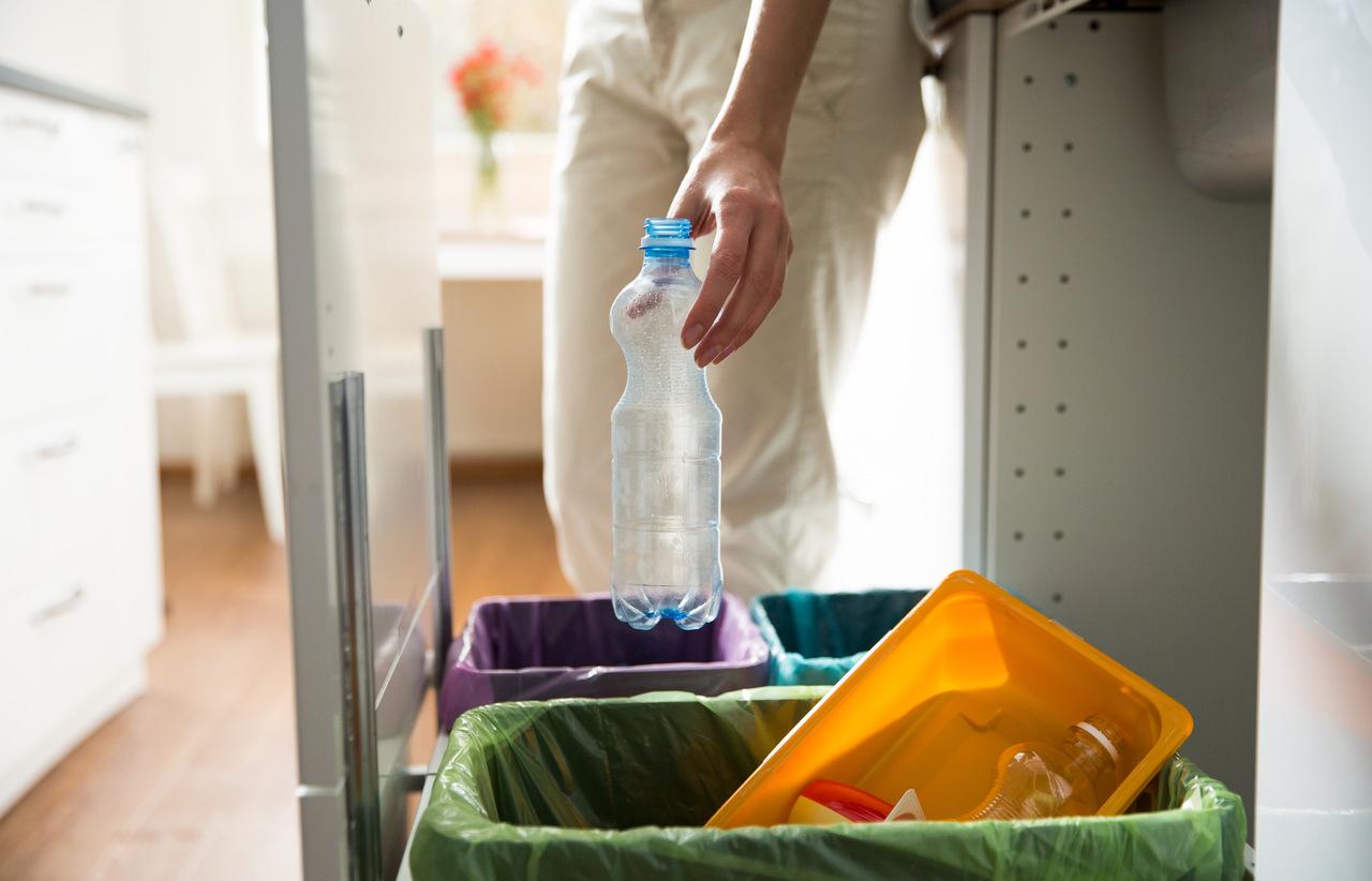 Segregacja śmieci: mężczyzna wyrzuca butelkę do kosza